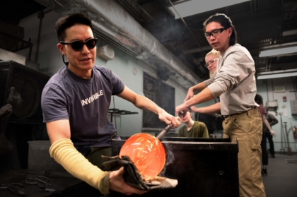 student and instructor blowing glass