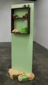 sculpture of free standing green wall with shelf and abstract objects