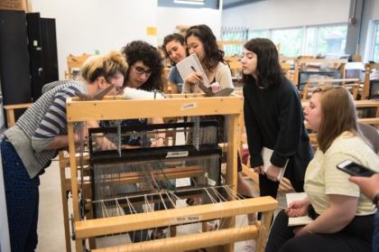 students weaving fiber