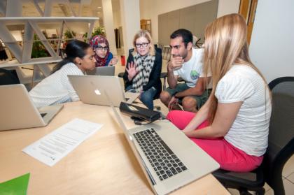 students huddled around computer at v c u arts qatar campus