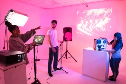 VCUarts Kinetic Imaging students arrange a multimedia project against an infinity wall.