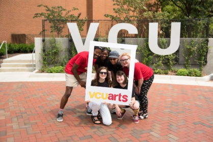VCUarts tour guides in front of VCU sign