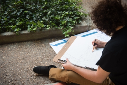 student drawing outside pollak building