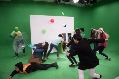 students throwing various props at green screen
