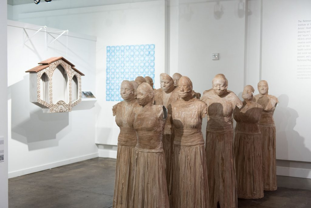Body casts of women victims of human trafficking stand in a group in the center of a gallery.