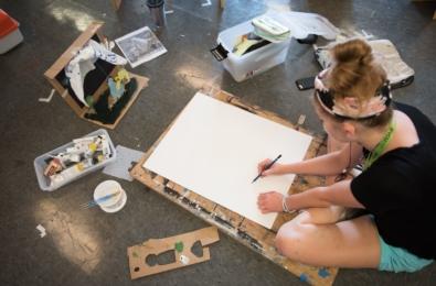 high school student sketching in sketchbook