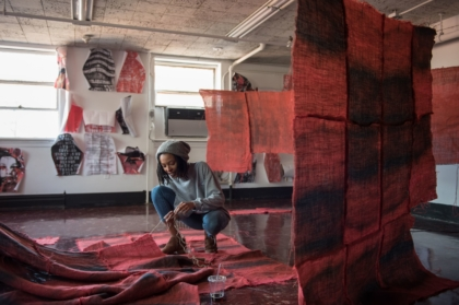 A student installing an exhibition with panels of red fabric
