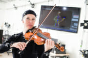 Susanna Klein wearing a black motion capture suit with nodes plays the violin while standing in front of a screen