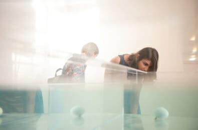 student examining sculpture installation
