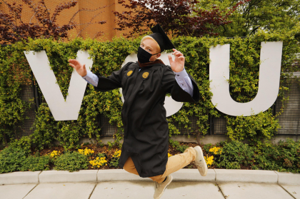 Student in cap, gown and mask, jumping in front of VCU sign