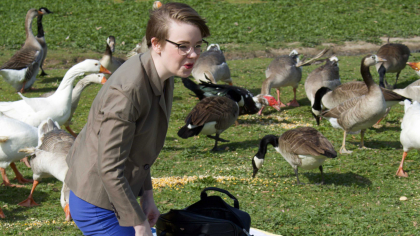 Laney Engle in a field surrounded by geese