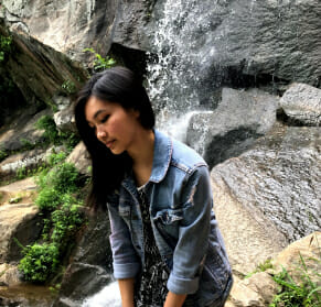 Michelle in a jacket sitting in front of rocks and a waterfall