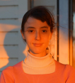 Headshot of Evie wearing a white turtleneck layered under an orange sweater. The photo appears to be taken outside a house at sunset