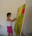Photograph of Eka wearing white top and pink skirt standing painting a large canvas at an easel