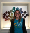Photograph of Emily in front of a wall-mounted glass peice. The artwork is made up of stone shaped glass orbs arranged by color against a white wall.
