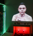 Documentation of video installation peice in which a video of Chelsea performing makeup contouring is projected against a wall above a mantel in a dark room. The room has green and red lighting in the fireplace and around the window