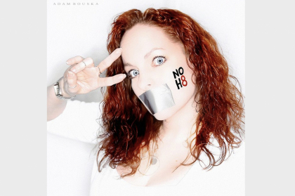 woman with tape over mouth holding peace sign