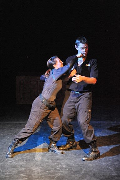 choreographed woman punching man on stage