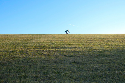 A single dancer, photographed from a distance, dances atop a grassy hill against a clear, blue sky